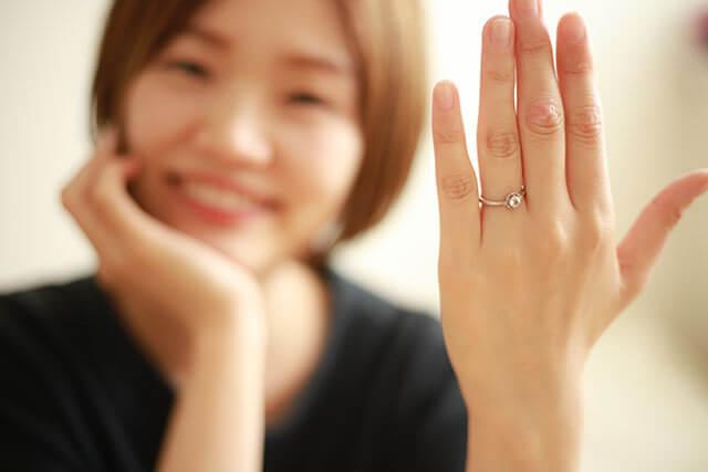 結婚指輪を電話でする女性