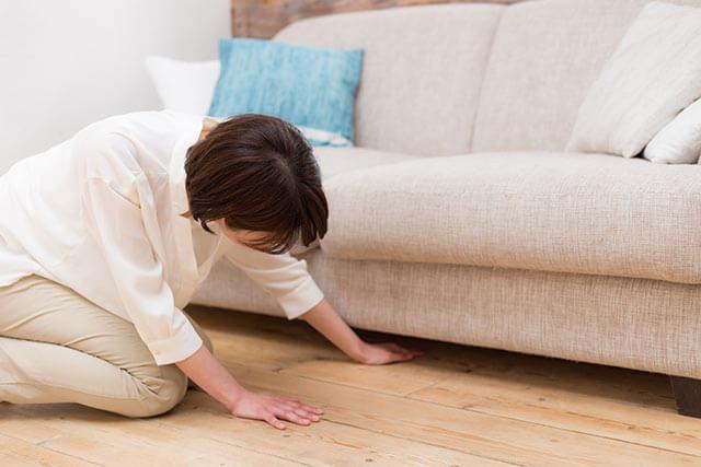 ソファーの下を探す女性