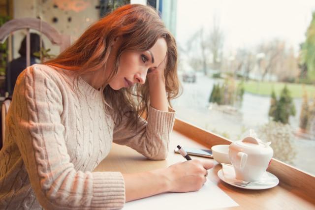 結婚報告はがきを送るか悩む女性